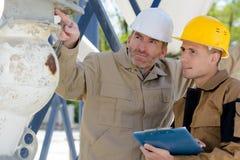 Två byggmästare som utomhus pekar på något arkivfoto