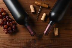 Två Cabernet - sauvignon vinflaska tvärt från direkt över på en mörk trätabell med druvakork- och korkskruv- och kopieringsutrymm arkivbild