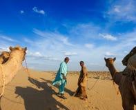 Två cameleers (kamelchaufförer) med kamel i dyn av Thar deser royaltyfri bild