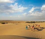 Två cameleers (kamelchaufförer) med kamel i dyn av Thar deser arkivfoto