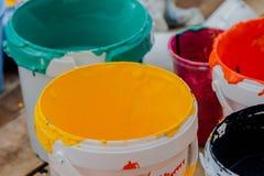 Två cans av akrylmålarfärger stänger övre och idérika kaos , selektivt Royaltyfri Foto