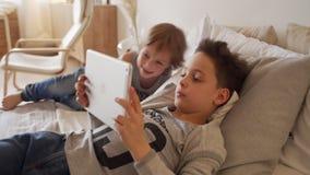 Två caucasian barn, pojkebröder som hemma spelar i säng på minnestavlan lager videofilmer