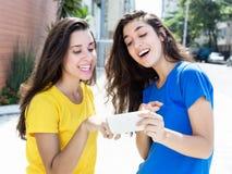 Två caucasian flickor som ser telefonen Arkivfoto
