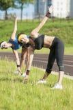 Två Caucasian flickvänner som har armar, och kropp som utomhus sträcker övningar Arkivbilder