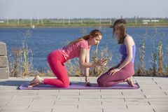 Två Caucasian kvinnlig i strumpbyxor och gymnastikskor som gör yogaövningar på bakgrunden av floden arkivfoto