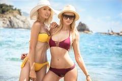 Två caucasian kvinnor som har gyckel på stranden royaltyfri fotografi