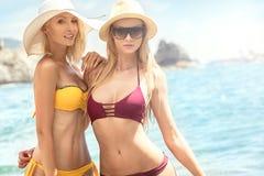Två caucasian kvinnor som har gyckel på stranden arkivbilder
