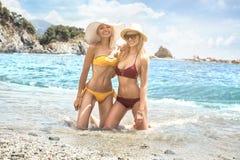 Två caucasian kvinnor som har gyckel på stranden royaltyfri bild