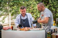 Två caucasian manliga shefs i den Budapest Ungern, som förbereder en kötträtt, utomhus- matlagning Arkivfoto