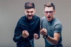 Två Caucasian personer man att uttrycka deras spänning och fröjd, genom att ropa ja royaltyfria foton
