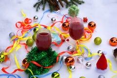 Två celebratory exponeringsglas av vin på bakgrunden av kulöra fläckar och magin av jul royaltyfri foto
