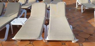 Två chaisevardagsrum för solbränt och att vila det tomma staget arkivbild