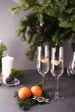 Två champagneexponeringsglas, granbranchs för glad jul, stearinljus, kort för hälsning för nytt år arkivbild