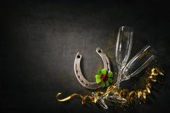 Två champagneexponeringsglas med en hästsko och en treklöver som lycklig cha arkivfoton