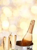 Två champagneexponeringsglas med flaskan. Royaltyfri Bild