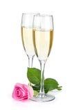 Två champagneexponeringsglas och rosa färgrosblomma Royaltyfri Foto