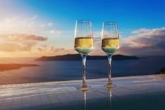 Två champagneexponeringsglas på kanten av oändlighetssimbassängen på solnedgången på den Santorini ön Royaltyfri Fotografi