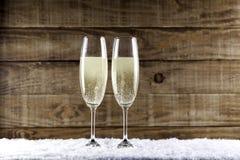 Två champagneexponeringsglas på snö royaltyfria bilder