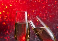 Två champagneflöjter med guld bubblar på rött ljusbokehbakgrund Arkivfoton