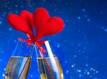 Två champagneflöjter med guld- bubblor och röda sammethjärtor gör jubel på blå bokehbakgrund Fotografering för Bildbyråer