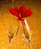 Två champagneflöjter med guld- bubblor och röda sammethjärtor gör jubel på guld- bokehbakgrund Royaltyfri Bild