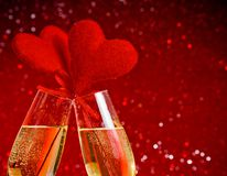 Två champagneflöjter med guld- bubblor och röda sammethjärtor gör jubel på röd bokehbakgrund Arkivbilder