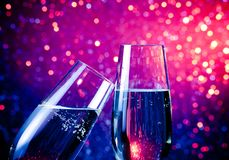 Två champagneflöjter med guld- bubblor på blått tonar ljus bokehbakgrund Arkivfoto