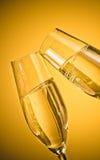 Två champagneflöjter med guld- bubblor på guld- ljus bakgrund Royaltyfri Foto