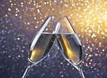 Två champagneflöjter med guld- bubblor på ljus bokehbakgrund Fotografering för Bildbyråer