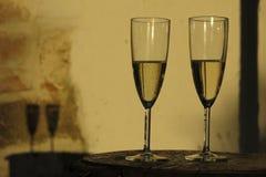 Två champagneflöjter som är upplysta vid guld- solljus Royaltyfria Foton