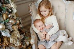 Två charma lilla systrar som sitter i en stol och ler i th Arkivfoton