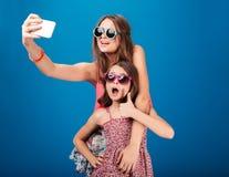 Två charma lyckliga systrar i solglasögon som tar selfie genom att använda smartphonen Arkivfoto