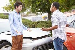Två chaufförer som argumenterar efter trafikolycka royaltyfria foton