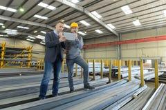 Två chefarbetare i lager med minnestavladatoren Royaltyfria Bilder