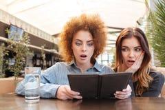 Två chockade kvinnor som ser räkningen i kafé Arkivbild