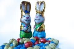 Två chokladeaster kaniner och chokladeaster ägg fotografering för bildbyråer
