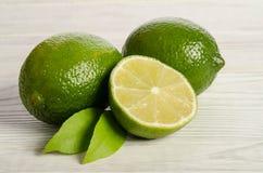 Två citroner med halva av saftig limefrukt på trätabellen arkivbilder