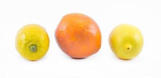 Två citroner och en apelsin på en vit bakgrund - sida och främre sikt royaltyfri bild