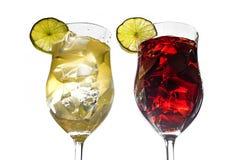 Två coctailexponeringsglas med vita och röda blandade drinkar från limefrukt, Royaltyfri Bild
