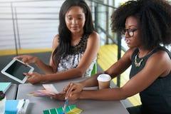 Två colleages som diskuterar idéer genom att använda en minnestavladator arkivfoto