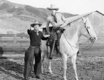 Två cowboyer och en vit häst (alla visade personer inte är längre uppehälle, och inget gods finns Leverantörgarantier som där wi Royaltyfria Bilder
