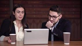 Två coworkers börjar att diskutera fall framme av bärbara datorn med kaffe lager videofilmer