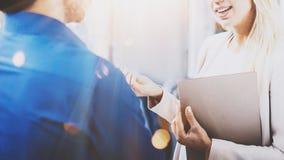 Två coworkers som diskuterar affärsprojekt i modernt kontor Lyckad säker latinamerikansk affärsman som talar med blondinen Royaltyfri Bild