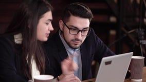 Två coworkers som diskuterar fall i ett kaffeavbrott med en bärbar dator arkivfilmer