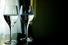Två crystal exponeringsglas som är fulla av vatten med grön bakgrund Royaltyfri Bild