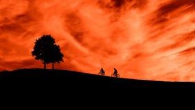 Tv? cyklister kl?ttrar kullen Solnedg?ng Romantisk bild