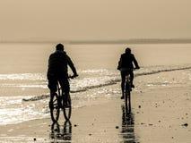 Två cyklister på stranden Fotografering för Bildbyråer