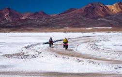 Två cyklister som går på vägen SjöLas Salinas peru Arkivfoton