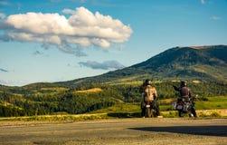 Två cyklister som tycker om solnedgång i berg Arkivfoto