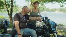 Två cyklister som utomhus meddelar nära motorcykeln